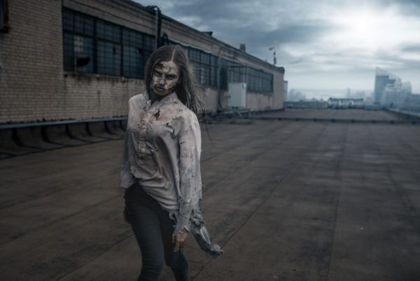 Female zombie on the roof of abandoned building