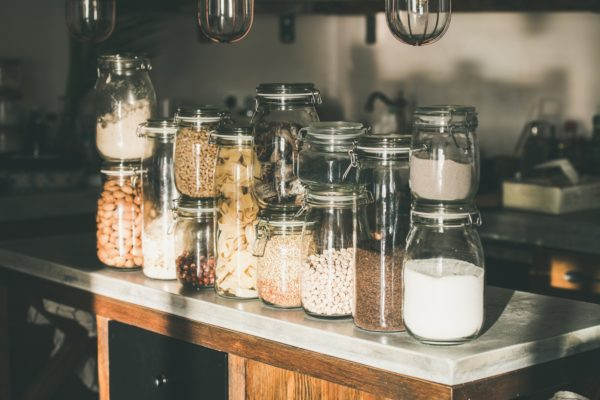 Grains, cereals, nuts, dry fruit, pasta in jars in kitchen