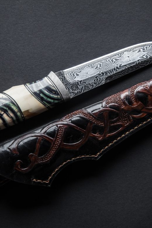 Hunter knife with wooden handle on a dark background