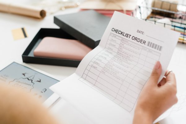 Paper with checklist order held by young female shopper looking through it